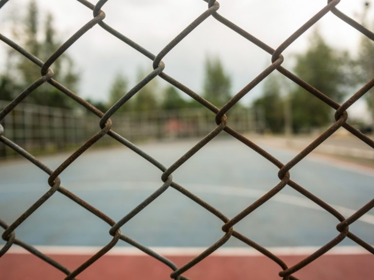 Chain link fence surrounding a basketball court