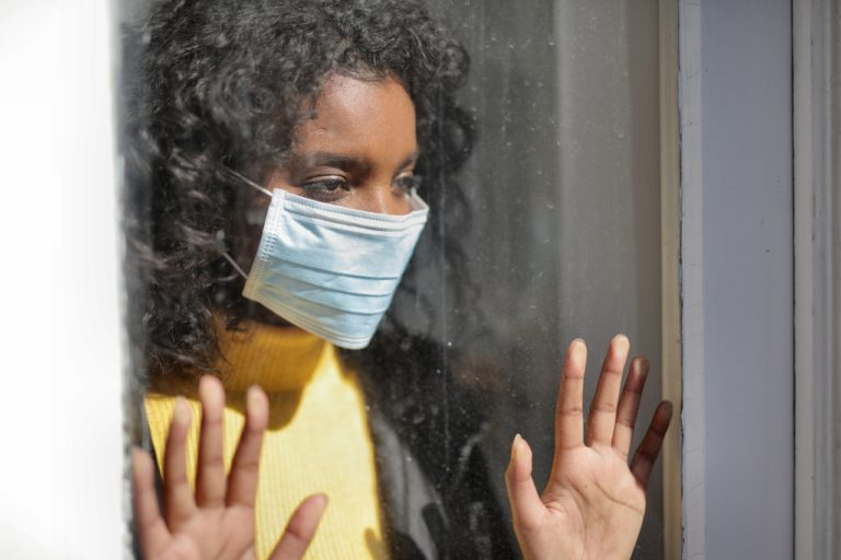 woman wearing facemask staring outside the window