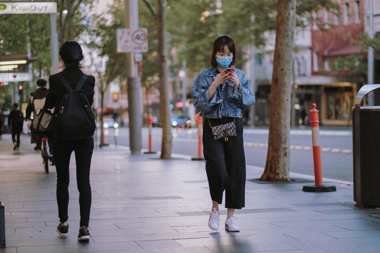 woman walking outside wearing facemask